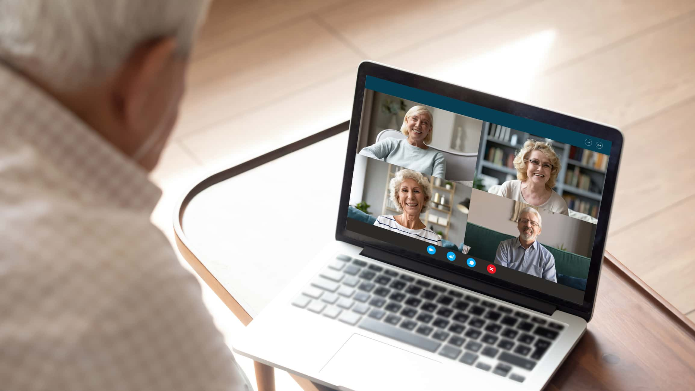 Senior citizen participating in an online video chat with his senior friends